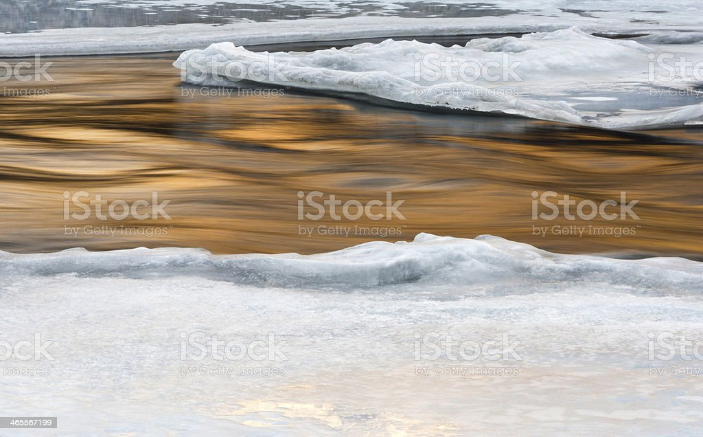 Goldenn flowing water with ice and snow royalty-free stock photo