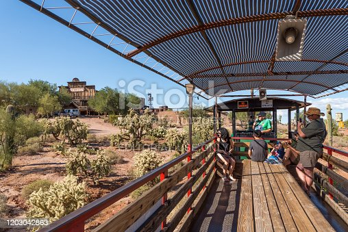 An engineer takes people on a ride around Goldfield Ghost Town, an old abandoned mining town in Apache Junction, Arizona that has been refurbished into a tourist attraction. It is located outside Phoenix near the Superstition Mountains, where the legend of the Lost Dutchman's gold originated.
