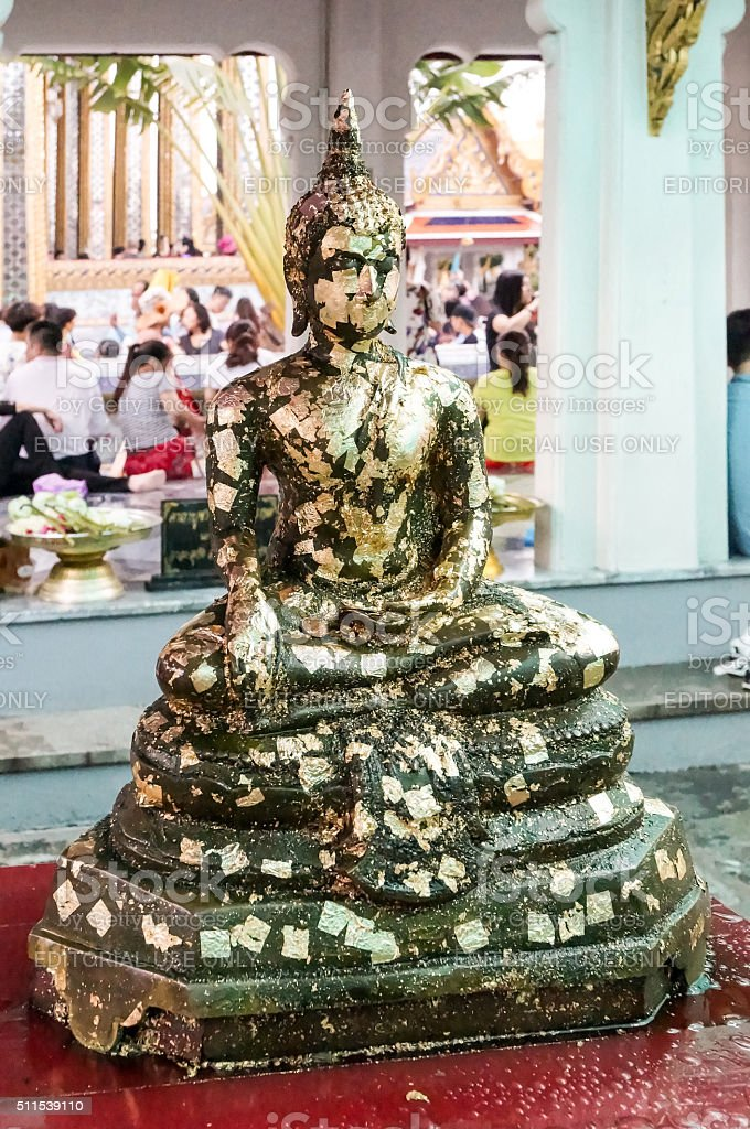 Gold-leaf Buddha Statue at Grand Palace in front of Tourists stock photo