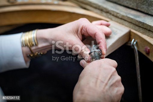 Close up of a Goldsmith's hands at work creating a silver ring in her workshop. Colour, horizontal with some copy space.