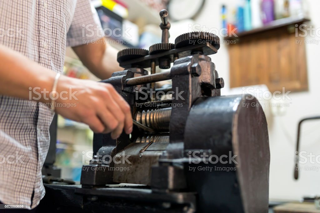 Goldsmith crafting metal with the help of a press royalty-free stock photo