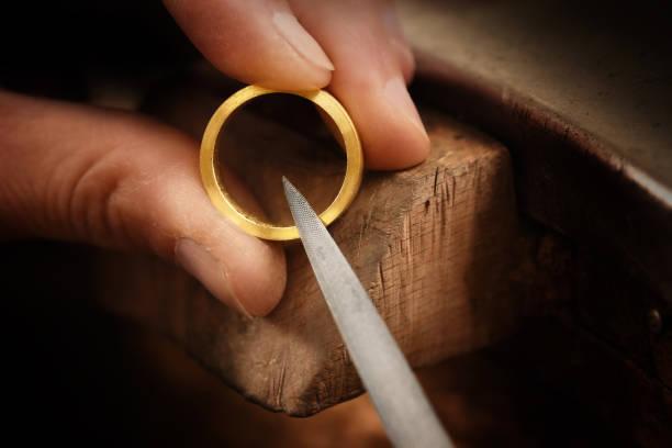 goldsmith hand håller ett gyllene ring och fungerar på det med en metal fil, på nära håll med kopia utrymme, fokus, smala skärpedjup - hand gold jewels bildbanksfoton och bilder