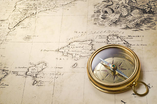 Goldtone compass laying on an old world map stock photo
