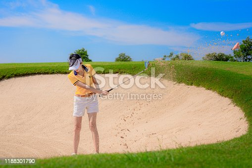 Woman golf player in action of hitting golf ball away from a trouble sandbank bunker in golf course, trouble away keep going concentrate to final destination