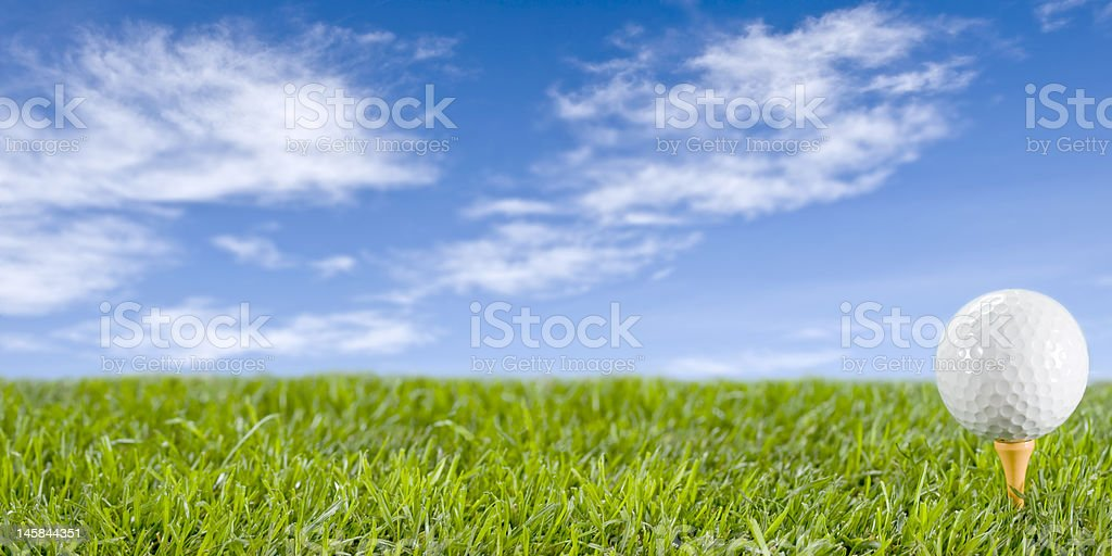 A golf all on a yellow tee stuck in the grass royalty-free stock photo