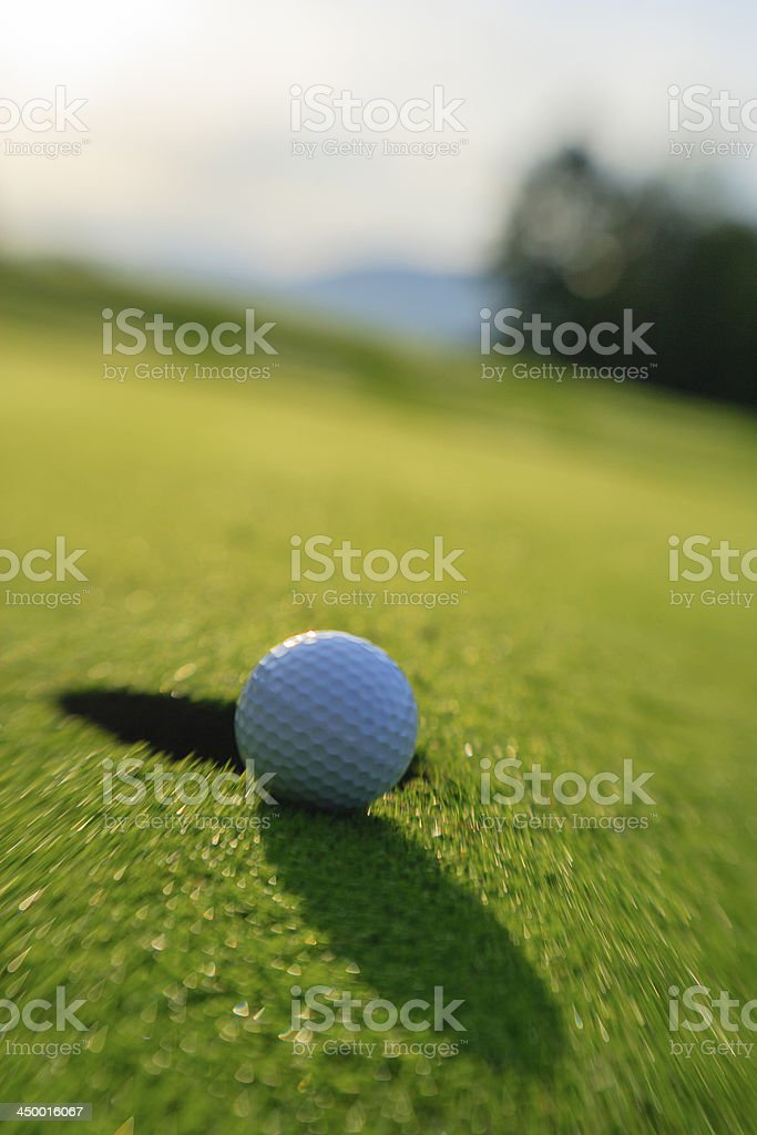 Golf ball about to drop in the hole. stock photo