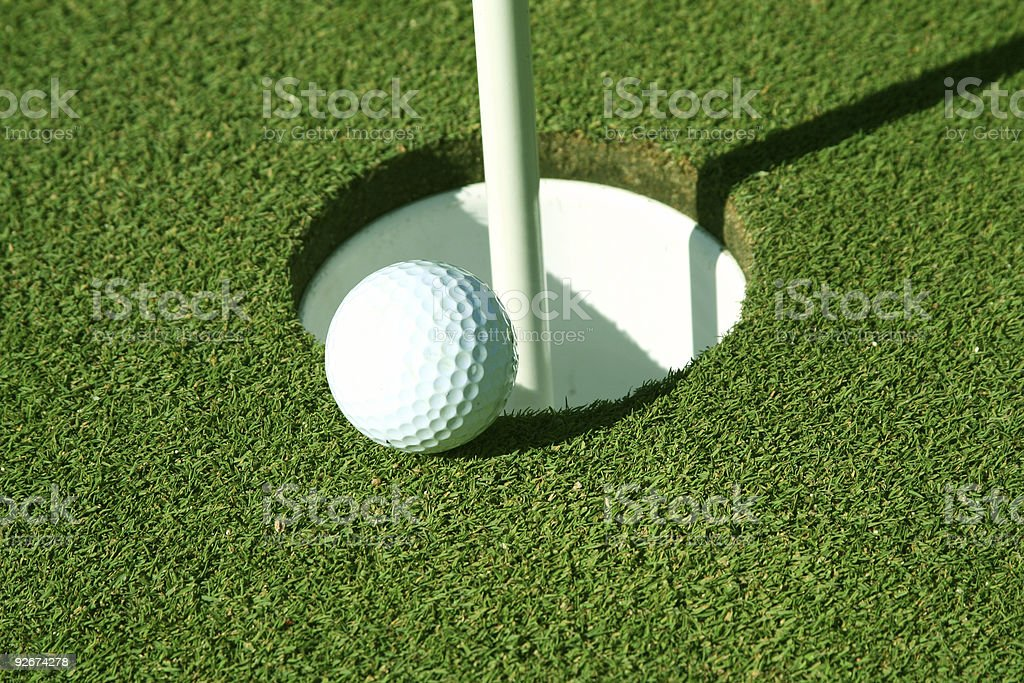 Golf ball about to go in hole royalty-free stock photo