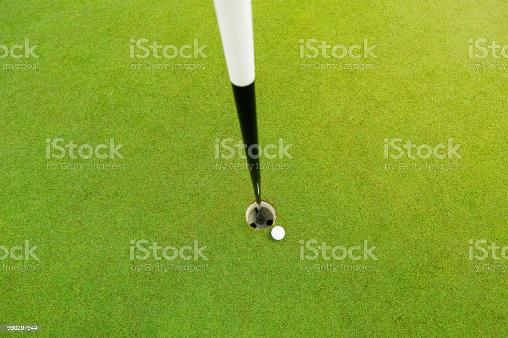 White golf ball near the hole on the green grass