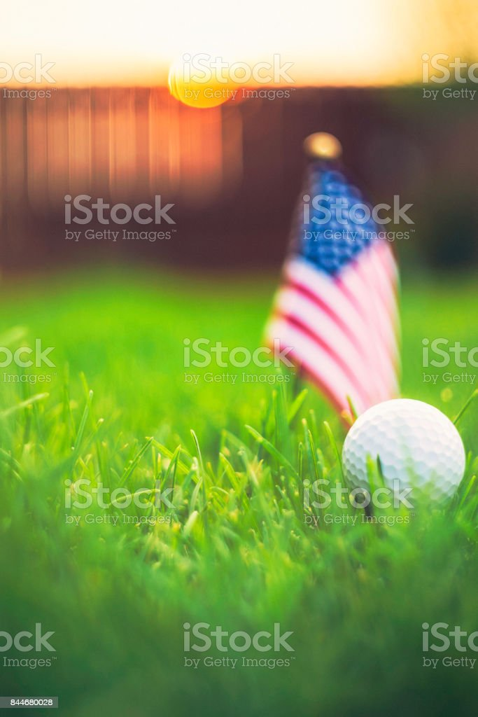Golf ball and American flag in grass with sunlight at dusk stock photo