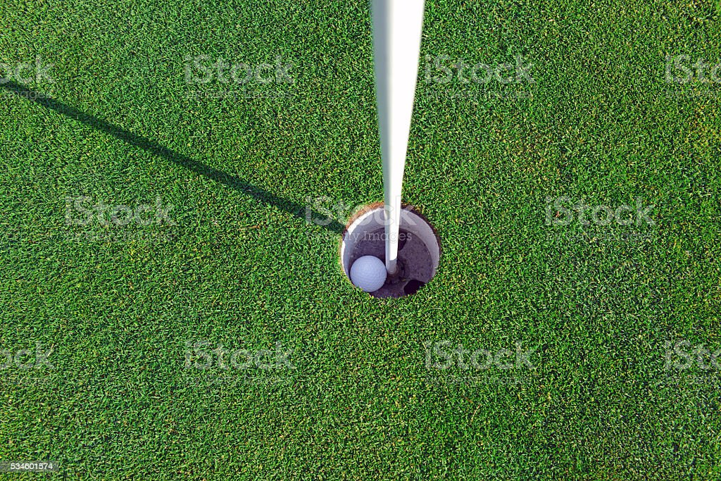 Golf ball and Flagstick of  Manicured grass of putting green stock photo