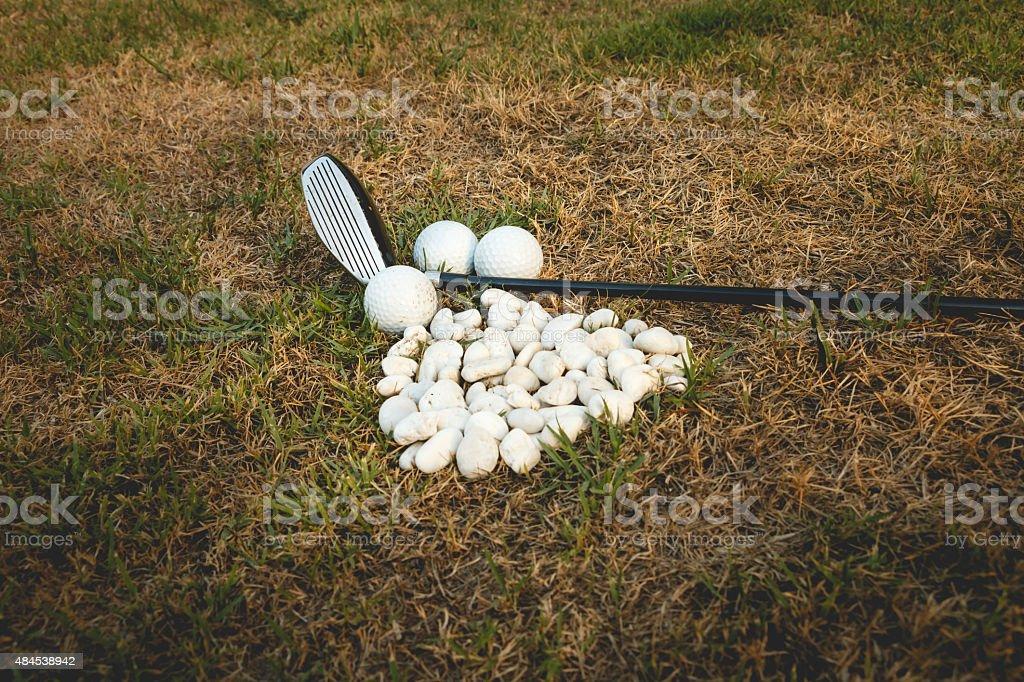 Golf ball and Golf club beside mini stone stock photo