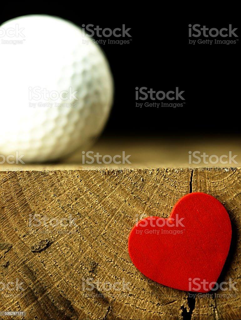 Piłka do golfa i serca na krawędzi stołu. – zdjęcie