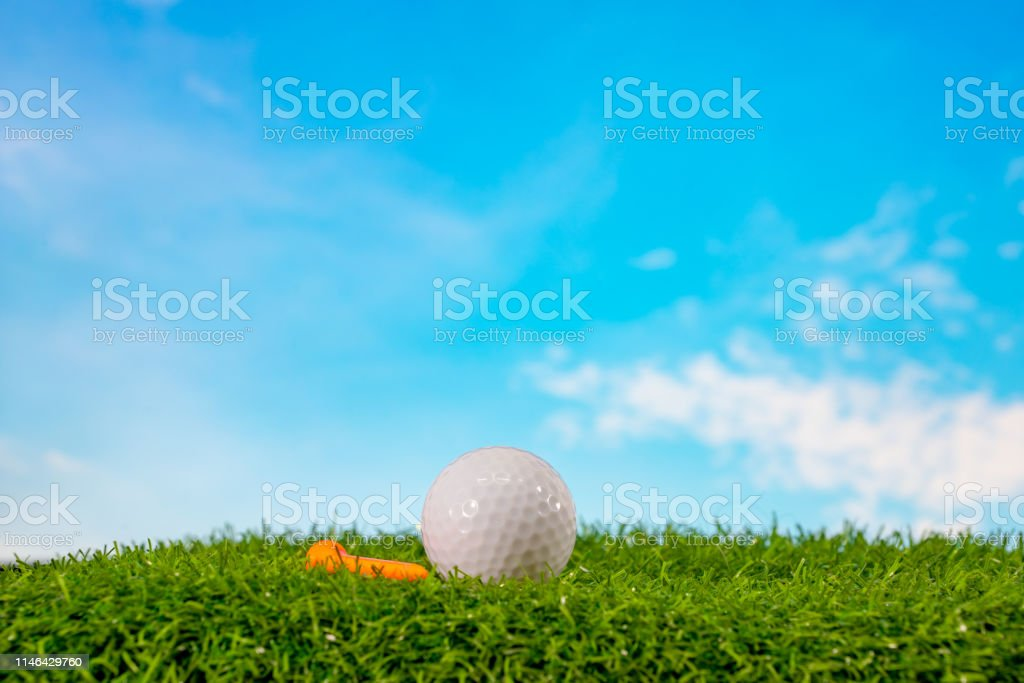 Golf ball and tee in tee off zone on grass and blue sky and cloud...