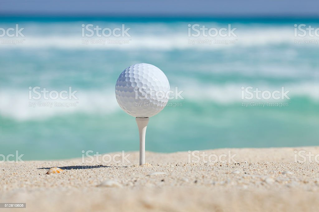 Golf ball and tee on beach with ocean waves behind stock photo