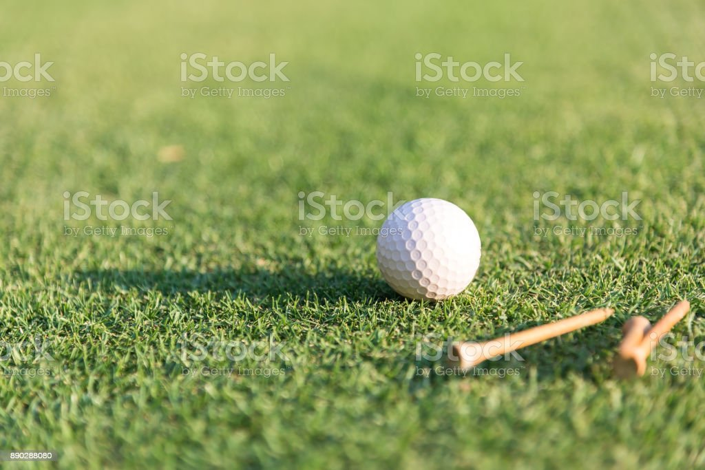 Golf ball and tee on green grass background. stock photo