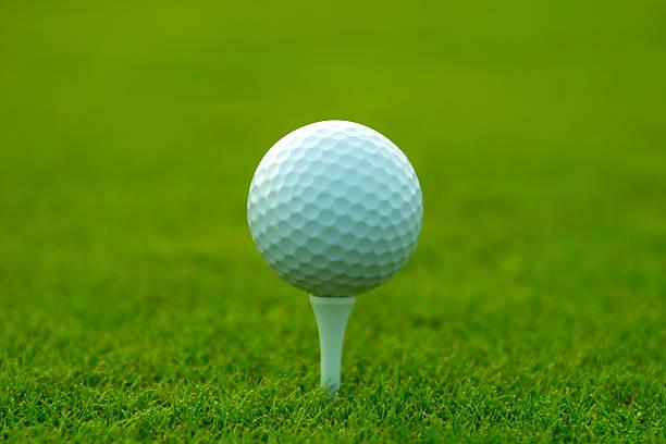 Golf ball and tee shallow dof stock photo