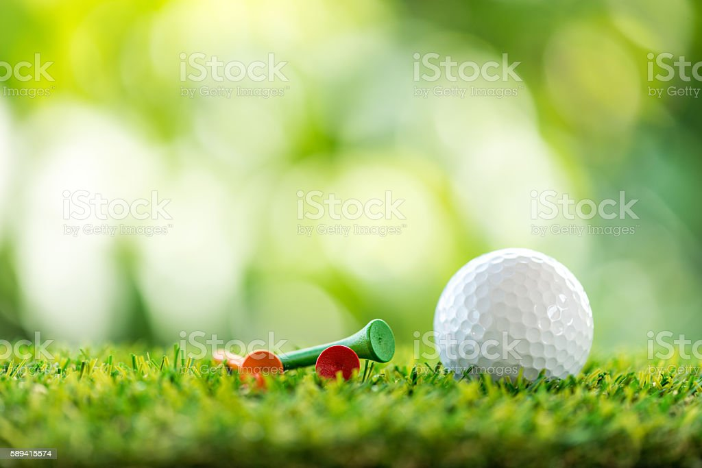 golf ball and wooden tee on grass stock photo