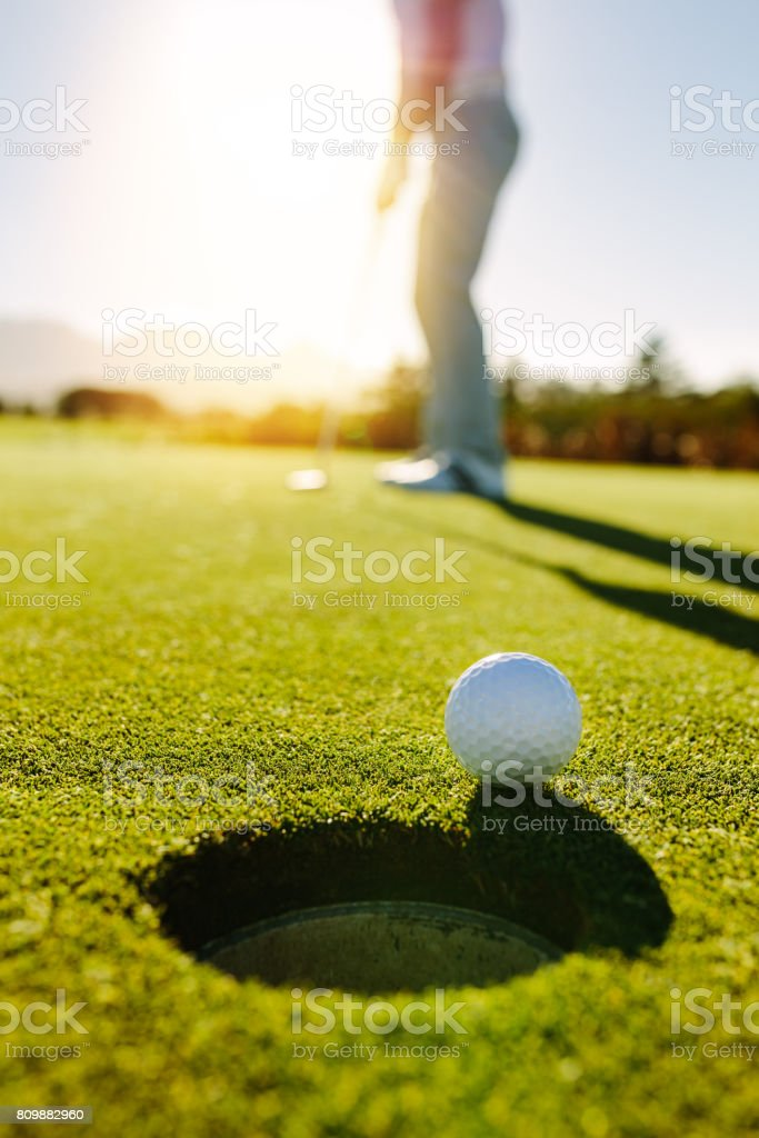 Golf ball at the edge of hole with player in background stock photo