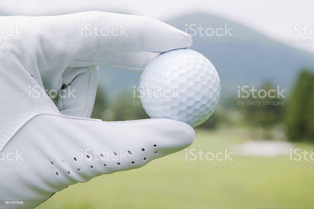 Golf ball being held by gloved hand, close-up