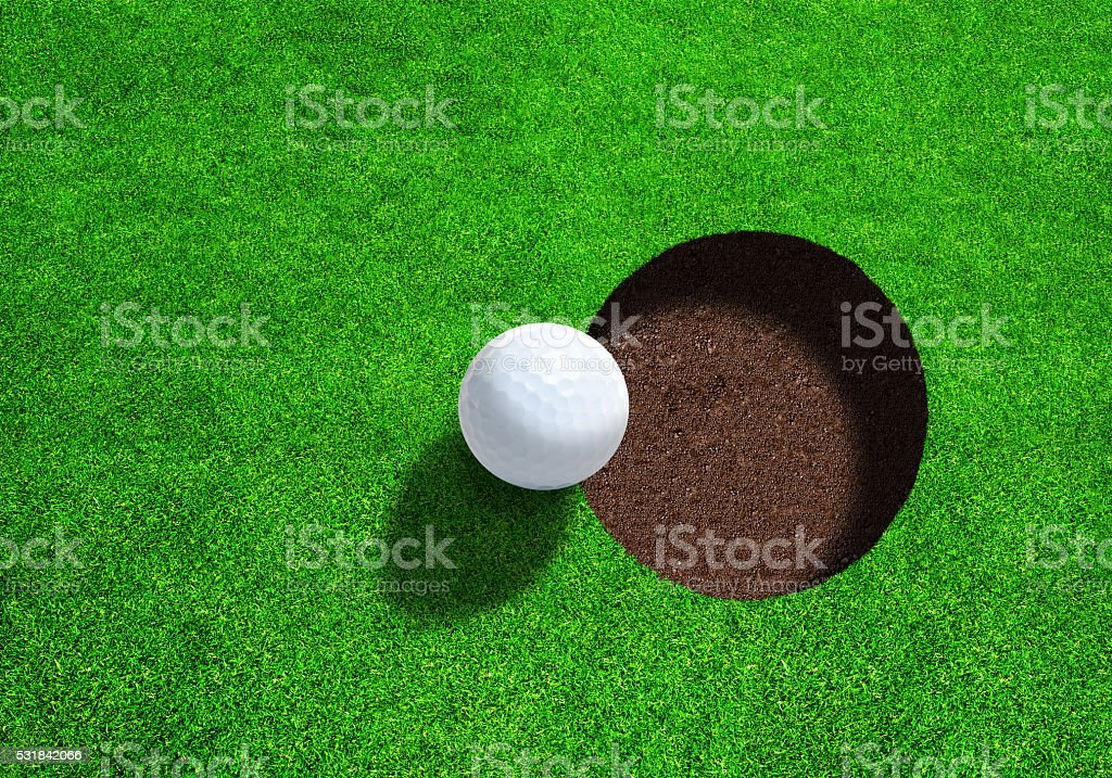 Golf Ball Close to Hole With Copy Space. Top View. stock photo