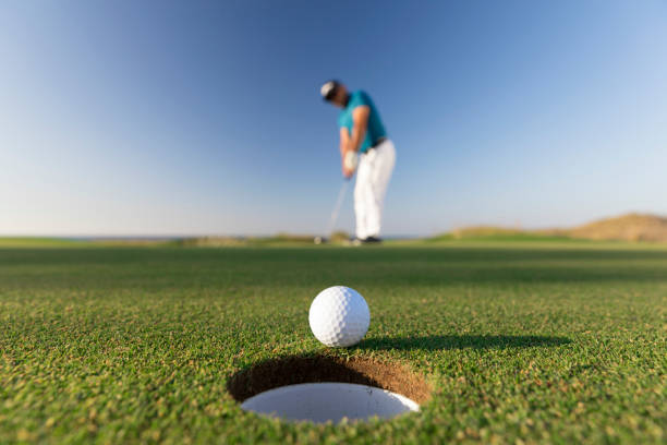 golf ball entering the hole after successful stroke - close up -  links golf - accuratezza foto e immagini stock