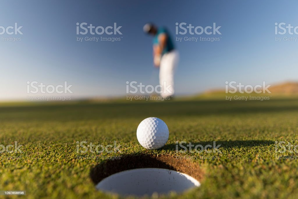 Golf ball entering the hole after successful stroke - Close up -...