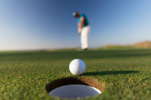Golf ball entering the hole after successful stroke - Close up -  Links Golf stock photo