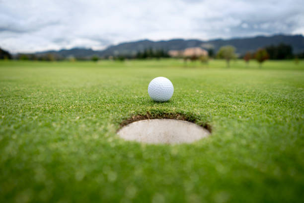 Golf ball going into the hole in the putting green stock photo