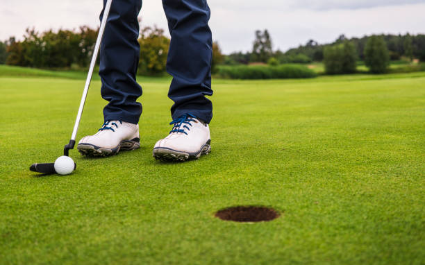 golf ball hitting on green and falling into hole stock photo