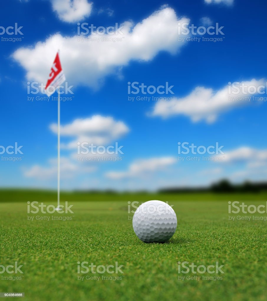 Golf ball in front of flag stock photo