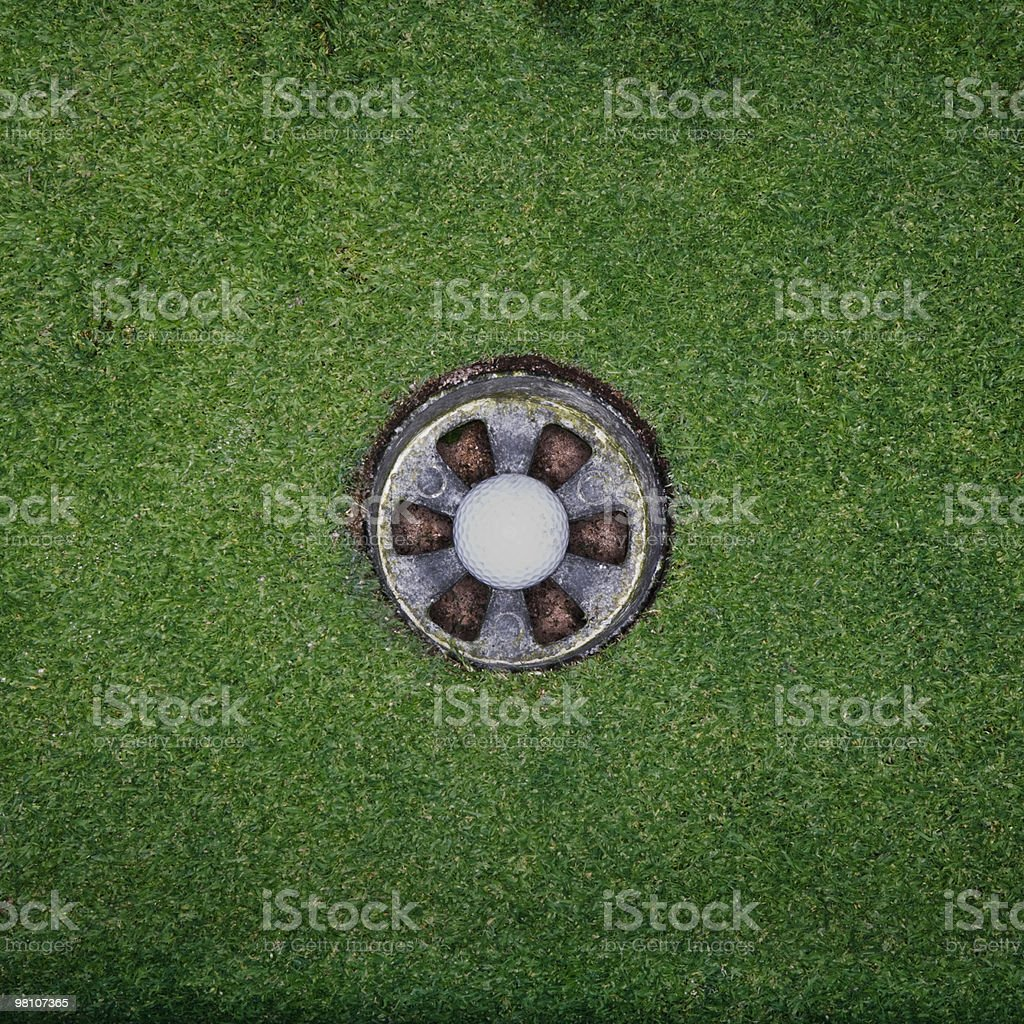 Golf ball in hole royalty-free stock photo