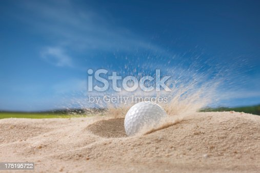 golf ball fell on sand trap causing the sand flying