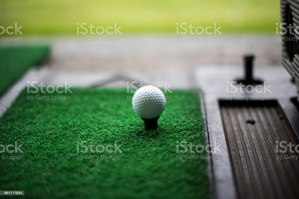 Golf ball on artificial green grass place with tee for practice...