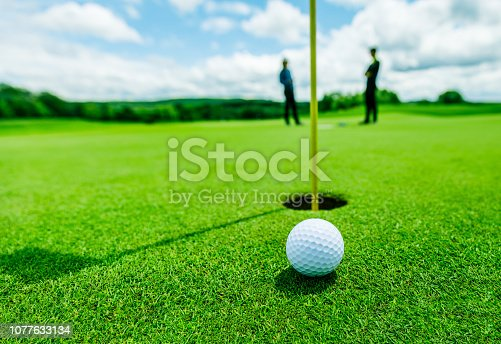 golf ball in the green grass close to the hole with the shadow of the flagpole and two blurred guys in the background