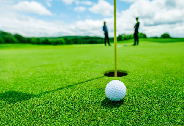 golf ball in the green grass, almost in the hole and two blurred golf players - golf foto e immagini stock