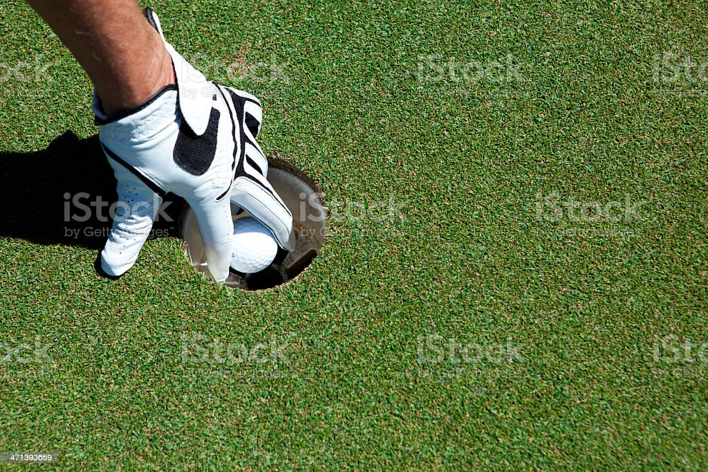A golfer retreives his golf ball from the cup.