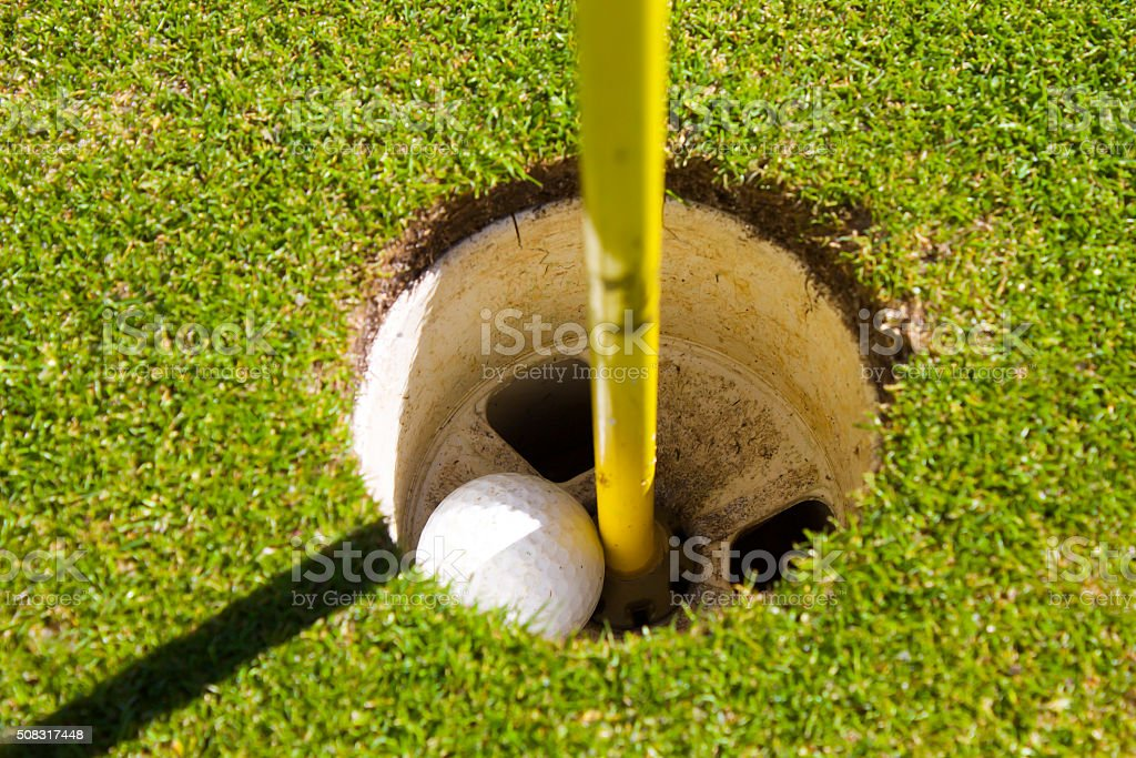Golf Ball Inside Cup on Putting Green Close Up stock photo