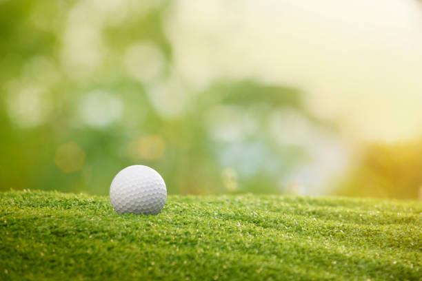 golfball ist auf einem grünen rasen in einem schönen golfplatz - golf stock-fotos und bilder