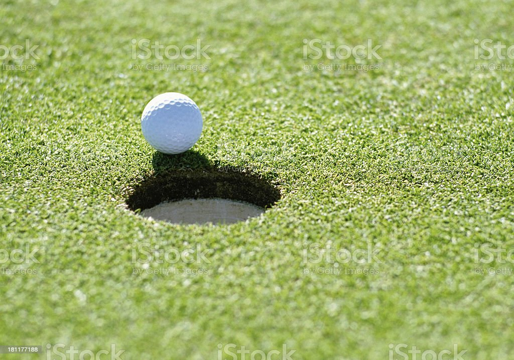 A golf ball just about to go in the hole from a long putt