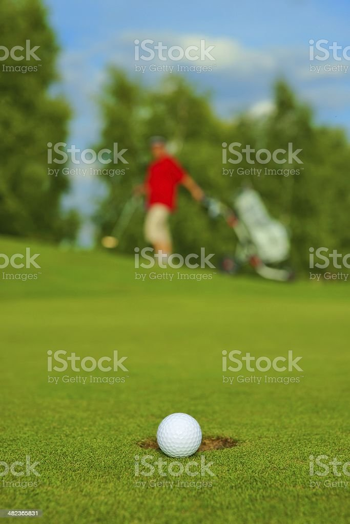 Golf, ball lying on the green next to hole royalty-free stock photo