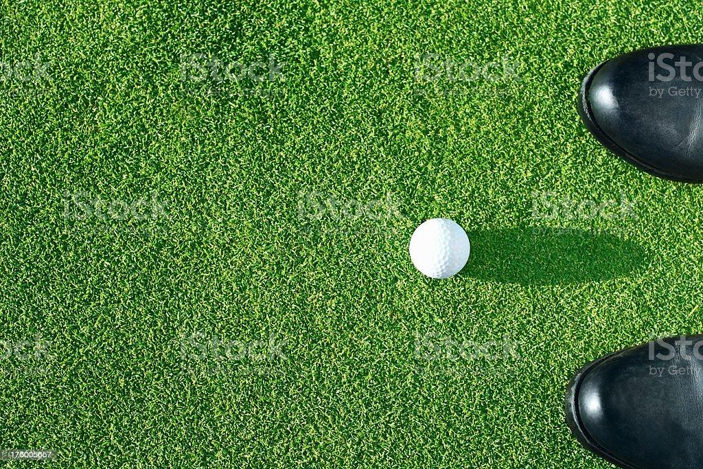 Golf ball near a pair of shoes