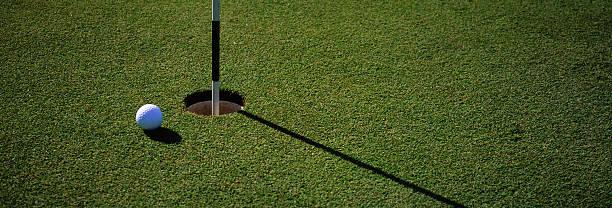 Golf Ball Near Hole stock photo