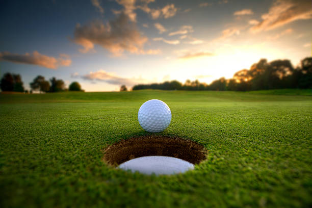 golf ball near hole - golf stock photos and pictures