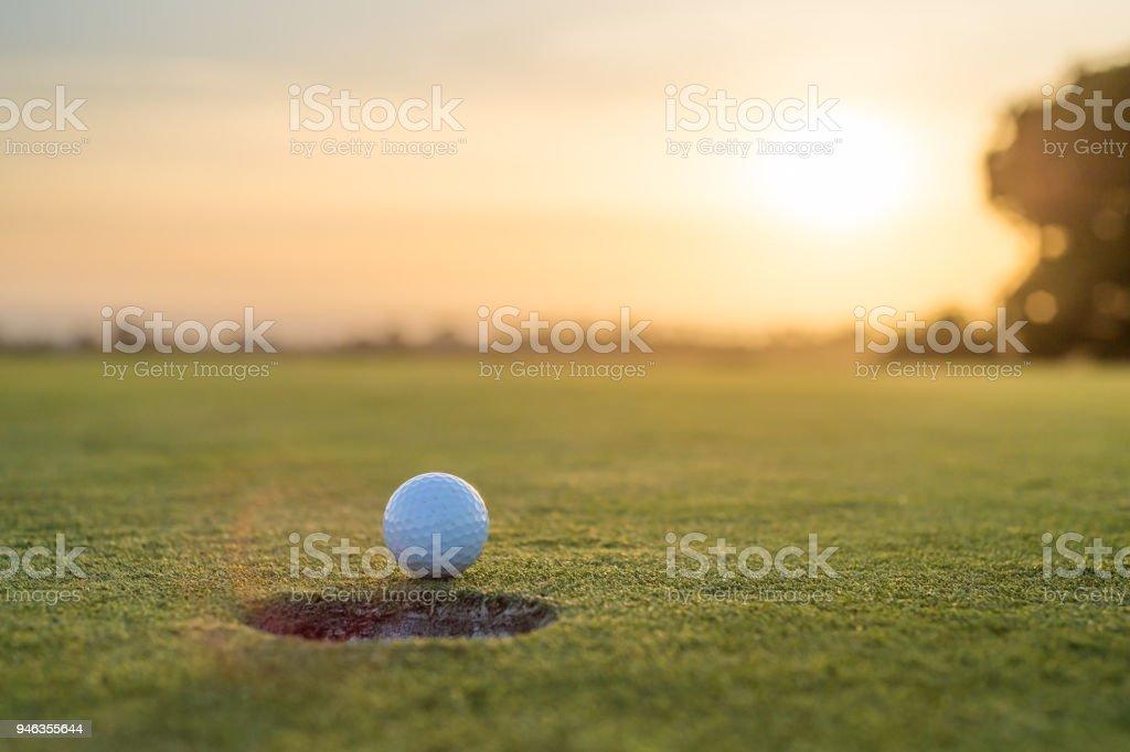 Golf Ball Near The Hole At Sunset