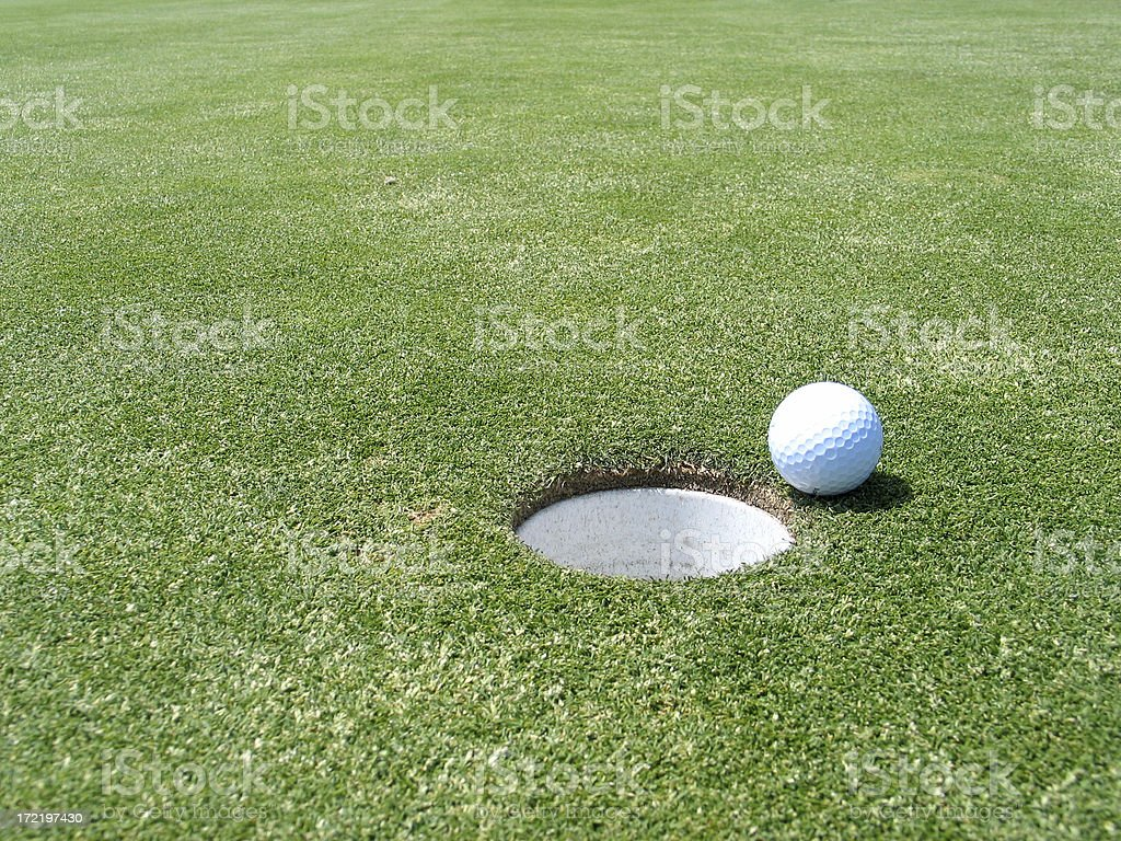 Golf Ball near the hole Golfball next to the cup on the green. Approaching Stock Photo