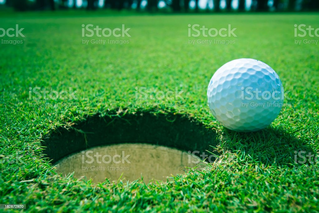 Golf ball near the hole royalty-free stock photo