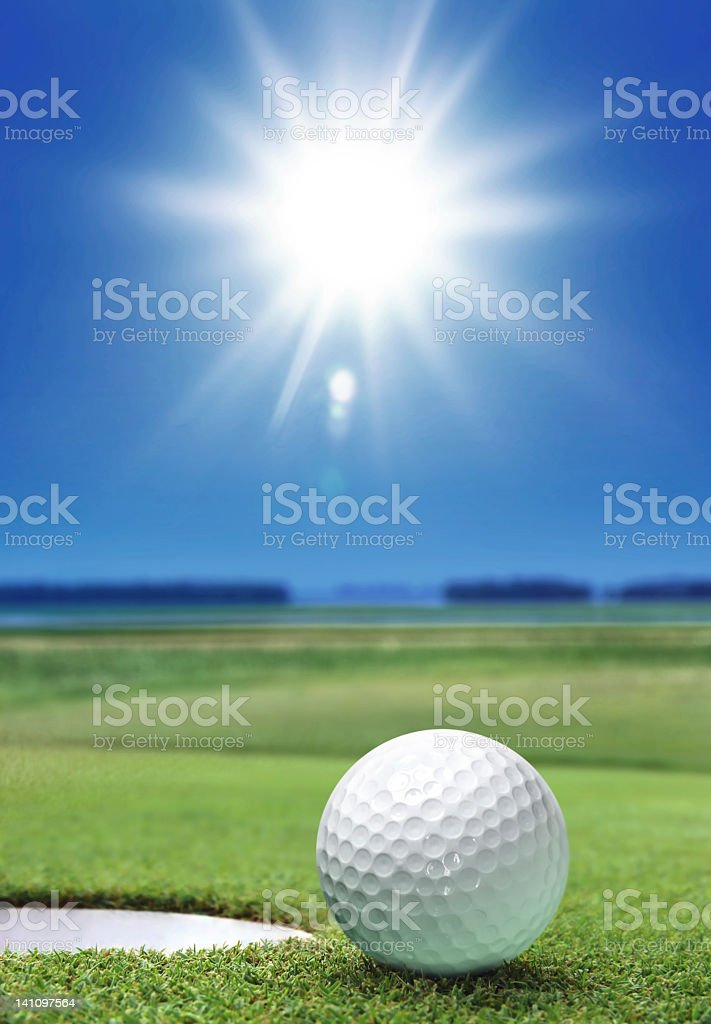 Golf ball next to hole in green course on a bright day  stock photo