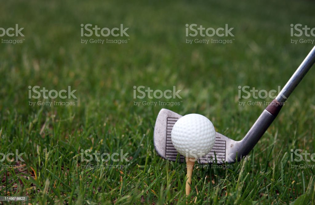 Golf ball on a tee and club ready to strike make a golfing background