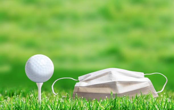 Golf Ball on a Tee and Face Mask on a  Golf Course During COVID-19 stock photo