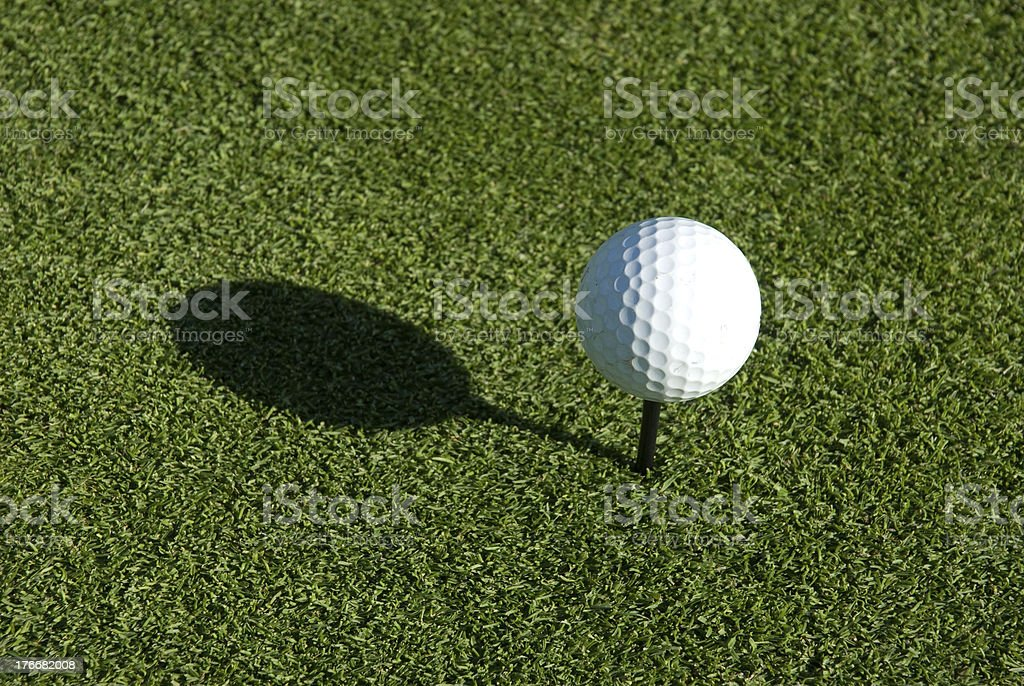 Golf ball on a tee in the sun royalty-free stock photo
